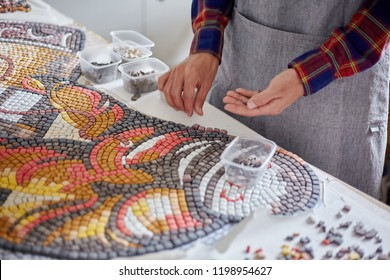 Faceless shot of man arranging mosaic pieces in colorful ornamental image