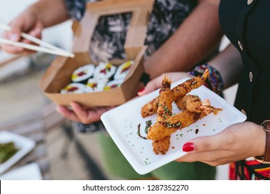 Faceless shot of man with sushi and woman with plate of fried shrimps standing outdoors