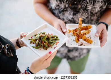 Faceless shot of man and woman holding plates of edamame and fried shrimps enjoying street food outdoors