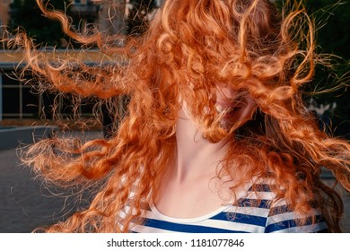 Faceless shot of red haired girl with her curly hair fly in air while she shaking her head closeup image