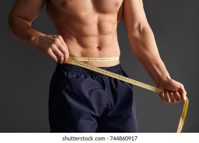 Faceless shot of shirtless man measuring waist with tape on gray background.