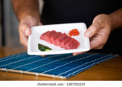 Faceless shot of street food chef showing plate with served slices of tuna and red caviar