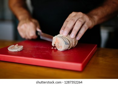 Faceless shot of street food chef slicing fresh tuna fish on cutting board