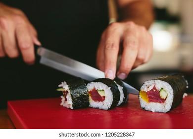 Faceless shot of street vendor cutting sushi in portion serving for meal