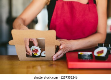 Faceless shot of woman in apron putting freshly made sushi in carton box to go