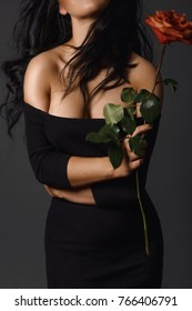 Faceless shot of woman in black dress posing alluringly holding red rose.