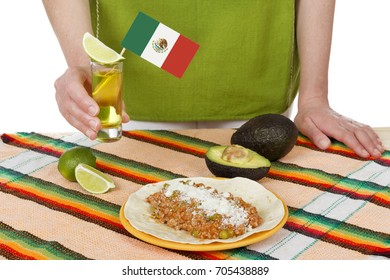 Faceless shot of woman holding tequila shot standing at table with traditional Mexican food.