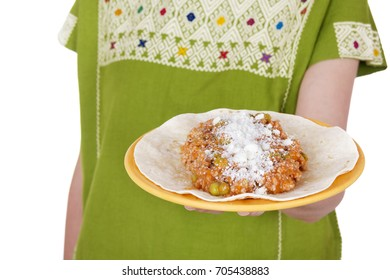 Faceless shot of woman in native Mexican clothing holding delicious national dish.
