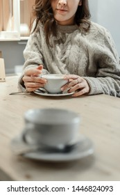 Faceless shot of woman's hands holding big mug of latte with an empty cup in front of her, selective focus