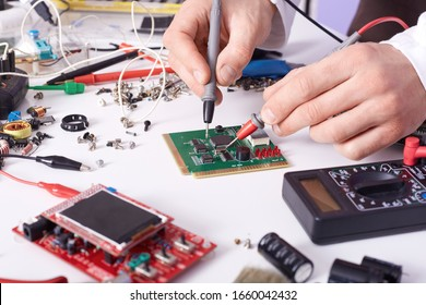 Faceless technician repairing smartphone's motherboard in lab, radioman soldering spare part of computer. Concept of computer hardware, mobile phone, electronic, repairing, upgrade and technology.