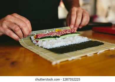 Faceless view of chef rolling sushi with makisu working in food truck on street