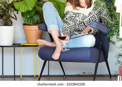 Faceless view of woman in sweater and denim having glass of wine using tablet in armchair.