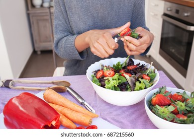 Faceless view of woman's hands mid section preparing organic vegetarian salad, slicing strawberries in home kitchen interior. Female with fresh ingredients food, healthy eating diet, cooking indoors.