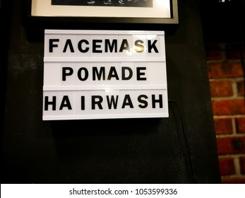 Facemask, pomade and hairwash written on the signboard in a hipster barber shop.