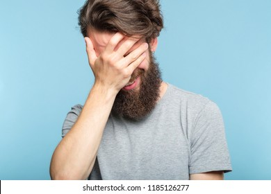 facepalm. ashamed embarrassed man covering his face. portrait of a young smiling bearded guy on blue background. emotion facial expression.