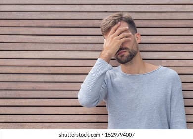 Facepalm. Ashamed embarrassed man covering his face. Young guy on wooden wall background with copy space. Emotion facial expression and feelings concept