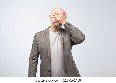 Facepalm facial expression. Portrait a disappointed mature man covering his face with his hand.