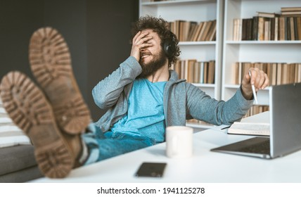 Facepalm. A young programmer works remotely at home. A young man smiles, covering his face with his hands sitting at a table in the office.