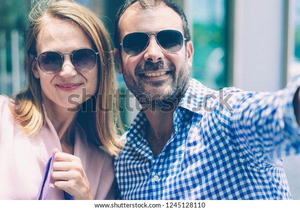 f560444e5fe5 Faces of happy mid adult couple wearing sunglasses taking selfie. Caucasian  woman holding shopping bag