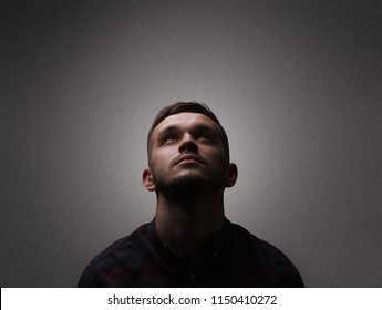 Facet portrait a man looking up. Dark lighting portrait bristle men in checkered shirt looks up with his head up on a dark gray background copy space