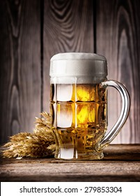 Faceted mug of light beer with foam and ears on the wooden background