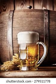 Faceted mug of light beer on a background of the old wooden barrels