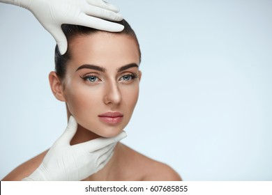 Facial Beauty. Portrait Of Beautiful Young Female With Perfect Makeup And Soft Smooth Skin. Closeup Of Beautician Hands In Gloves Touching Sexy Woman's Face. Plastic Surgery Concept. High Resolution