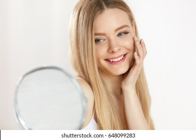 Facial Beauty. Portrait Of Sexy Young Woman With Fresh Healthy Skin Looking In Mirror Indoors. Closeup Of Beautiful Smiling Girl With Natural Makeup Touching Face. Cosmetic Concept. High Resolution