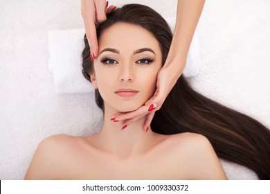 Facial Beauty Treatment. Closeup Of Beautiful Woman Getting Beauty Treatment, Hand Massage At Day Spa Salon. Massauer Massaging Female Face With Aromatherapy Oil. Skin And Body Care. High Resolution