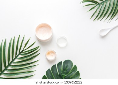 facial and body spa. face cream on the background of tropical leaves of Monstera palm on white background isolated