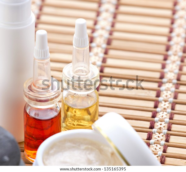 facial and body  spa-cosmetics products on bamboo mat on blurred background