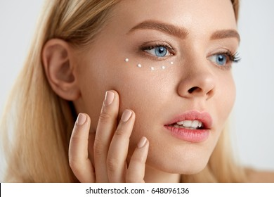Facial Care. Portrait Of Sexy Young Woman With Drops Of Cosmetic Cream On Skin Under Eyes. Closeup Of Beautiful Female With Beauty Product On Soft Skin, Natural Makeup Touching Face. High Resolution