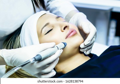 Facial cleansing, vacuum hydro peeling. Young woman enjoying a radiant face in a beauty salon, facial skin care by a cosmetologist, professional doctor, freshness and modern technology