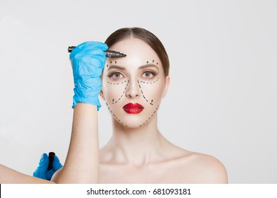 Facial cosmetic plastic surgery. Doctor surgeon hand in glove draw wrinkle lines on Woman face isolated white background. Sculpting reshaping Wrinkles fat removal cosmetic filling operation concept