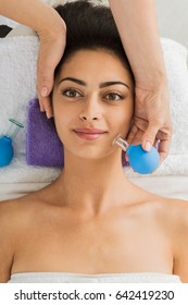 Facial cupping vacuum massage in spa. Beautiful girl in wellness center. Professional relaxation procedure to attractive young indian girl in beauty parlor, top view
