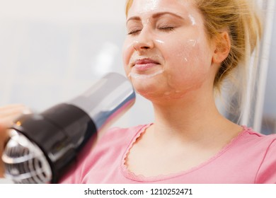 Facial dry skin and body care, complexion treatment at home concept. Woman drying her gel peel off face mask using hair dryer