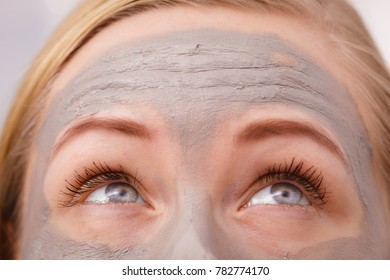 Facial dry skin and body care, complexion treatment at home concept. Closeup of woman having grey mud mask on face, eyes looking up above.