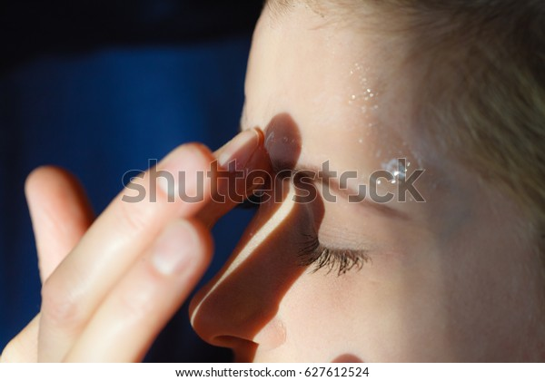 Facial dry skin and body care, complexion treatment at home concept. Young woman applying gel mask on her face.