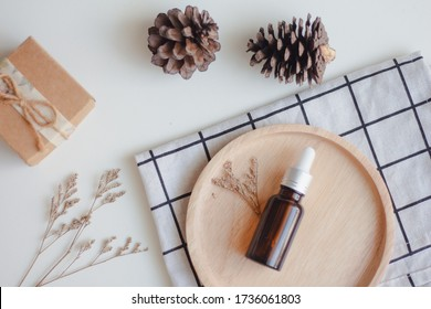 Facial essential oil or serum packaging on wood tray on white background. Beauty cosmetic product for skincare concept. Autumn and winter. Top view. Flat lay.