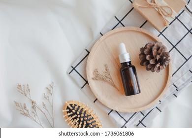 Huile essentielle faciale ou emballage sérique sur plateau en bois sur fond blanc. Produit cosmétique de beauté pour le concept de soins de la peau. Automne et hiver. Vue supérieure. Plat lay.