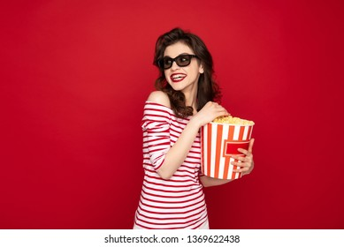 Facial expression concept. Waist up portrait of happy brunette woman in 3D glasses having fun while grasping pop corn box and refusing to share it. Isolated on red