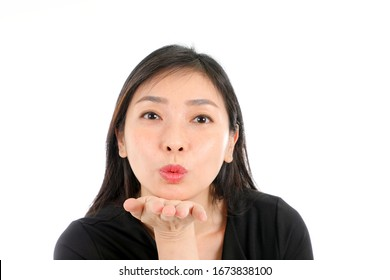 Facial Expression Young Asian woman office attire white background blow kiss palm of hand