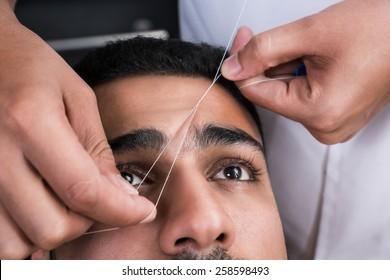 Facial hair removal eyebrows threading procedure in beauty salon