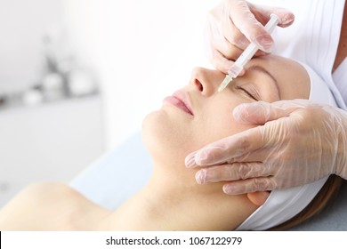 Facial injection with botulinum toxin.  Beautician cares for a woman's face during a rejuvenating procedure at a beauty clinic.