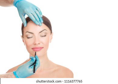 Facial lips cosmetic plastic surgery. Doctor hands holding face about to draw lines with marker on lips isolated on white background with copy space. Beautify concept