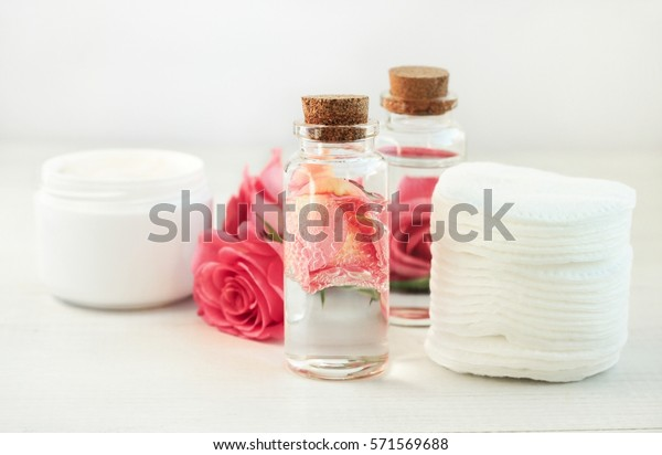 Facial lotion floral extract. Glass bottle with attar bubbles and rose petals, cotton pads. Healing homemade skincare moisture tonic. Gentle soft focus