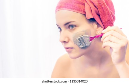 facial make up beautiful young woman applying cosmetic mascara using a brush on her pretty soft delicate skin on face looking at the mirror. she is covering her hair with a red towel.