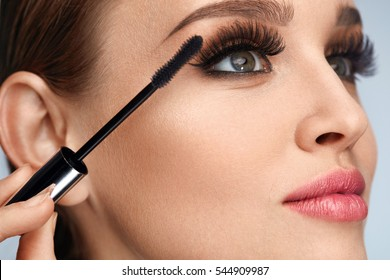 Facial Makeup. Beauty Woman Face With Fresh Healthy Skin And Perfect Professional Makeup. Young Woman With Long Fake Eyelashes Applying Black Mascara On Eyes With Brush. Cosmetics. High Resolution