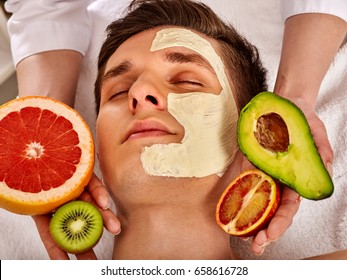 Facial mask from fresh fruits and clay for man. Beautician apply slices of avocado, grapefruit and kiwi. Male lying spa bed has skin care procedure in salon. Avocados main ingredient cosmetic masks.