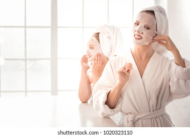 Facial mask. Happy pretty nice woman smiling and using a facial mask while caring about her skin